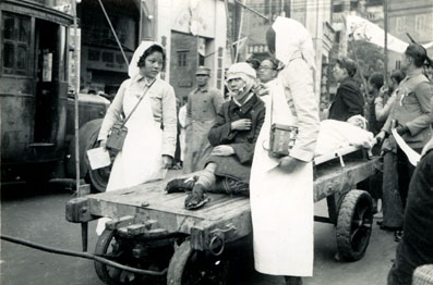 The wounded being taken to hospital on a cart, and attended by two Nurses, c.1938. Canton. Image from http://www.presbyterian.org.nz.
