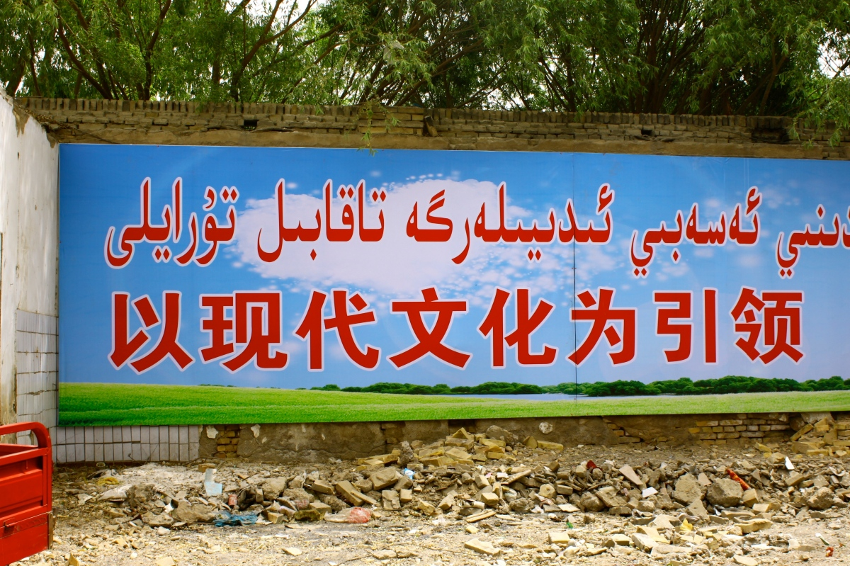 "Rough translation: ""Look to modern culture to lead the way."" Near the Kuche old town 老城, just nearby a Uighur dude passed out in his own vomit on the footpath. Image Kiwese."